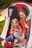 享受在露营地的马瑟和女儿野营假日 免版税图库摄影