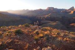 享受在马掌Mesa的两年轻女人日落在大峡谷 免版税库存照片