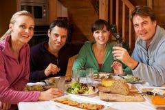 享受在高山瑞士山中的牧人小屋的组朋友膳食 图库摄影