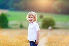 享受在麦田的愉快的白肤金发的孩子男孩日落 免版税图库摄影
