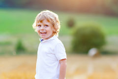 享受在麦田的愉快的白肤金发的孩子男孩日落 免版税库存照片