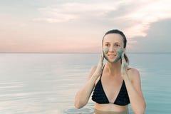 享受在死海backgr的妇女自然泥矿物来源 库存图片