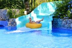 享受在aquapark的活跃男孩水滑道 免版税图库摄影