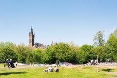 享受在Kelvingrove草坪的人们一个温暖的晴天打标准数 免版税库存图片