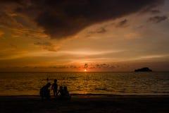 享受在Rodadero海滩,圣玛尔塔,哥伦比亚的人们美好的四种颜色日落 库存照片