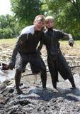 享受地方泥奔跑的一对泥泞的夫妇 免版税库存照片