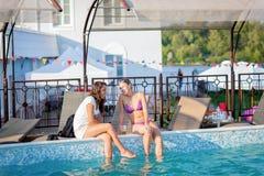 享受夏令时的愉快的朋友在游泳池党 免版税库存照片