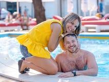 享受夏令时n的愉快的夫妇度假胜地游泳场 库存图片