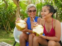 享受夏天休假的愉快和美丽的亚裔印度尼西亚少年女孩生活方式画象喝椰子在热带 免版税库存图片