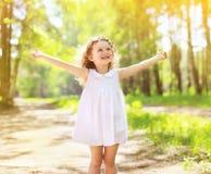 享受夏天晴天的正面迷人的卷曲小女孩 免版税库存照片
