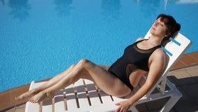 享受夏日的妇女在海滩胜地旅馆,接触光滑的depilated腿 晒日光浴由水池的夫人 股票视频