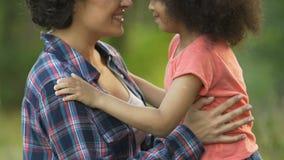享受夏日的母亲和女儿在庭院里外面,家庭通信 影视素材