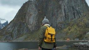 享受多雪的山峰视图的徒步旅行者 低角度后面视图有黄色背包的男性徒步旅行者和享用 股票视频