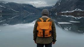 享受多雪的山峰视图的徒步旅行者 低角度后面视图有黄色背包的男性徒步旅行者和享用 影视素材