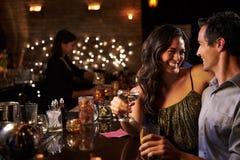 享受夜的夫妇在鸡尾酒酒吧 免版税图库摄影