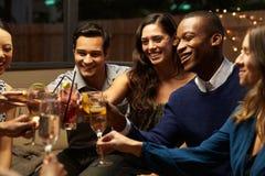 享受夜的小组朋友在屋顶酒吧 免版税库存图片