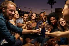 享受夜的小组朋友在屋顶酒吧 图库摄影