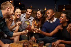 享受夜的小组朋友在屋顶酒吧 免版税库存照片