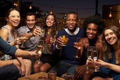 享受夜的朋友画象在屋顶酒吧 免版税图库摄影
