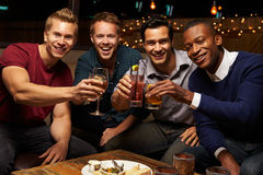 享受夜的男性朋友画象在屋顶酒吧 免版税库存照片