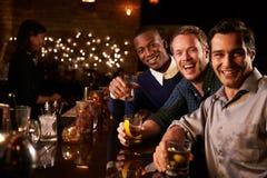 享受夜的男性朋友画象在鸡尾酒酒吧 免版税库存照片