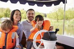 享受天一起在河的小船的家庭 库存照片