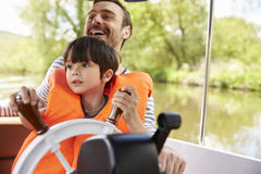 享受天一起在河的小船的父亲和儿子 免版税图库摄影