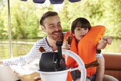享受天一起在河的小船的父亲和儿子 免版税库存照片