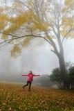 享受天的微笑的女孩在有雾的秋天森林里 免版税库存图片