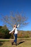 享受天的微笑的女孩在秋天公园 库存照片