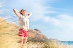 享受太阳的自由的愉快的妇女在度假 库存图片