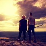 享受奇妙片刻的夫妇在日落期间 年轻对岩石手表峰顶的远足者在谷的对太阳 库存图片