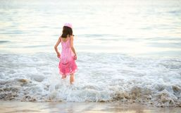 享受女孩粉红色的礼服挥动年轻人 免版税库存图片