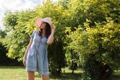 享受她的时间外部的可爱的年轻女人在有日落的公园在背景中 库存照片