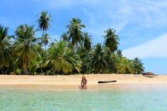 享受她的时间和休息接近南部的海滩的海的年轻美丽的妇女Pelicano海岛,巴拿马 免版税库存图片