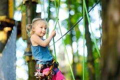 享受她的时间的可爱的小女孩在上升的冒险公园在温暖和晴朗的夏日 库存图片