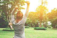 享受她的时间的可爱的少妇外面在有su的公园 免版税库存照片