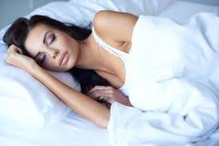 享受安闲之夜睡眠的少妇 免版税库存照片