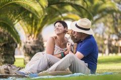 享受室外娱乐活动的快乐的白种人夫妇坐与幼小疯狂的狗的绿草在城市和戏剧 图库摄影
