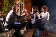 享受室外晚餐的成熟朋友在Firepit附近 图库摄影