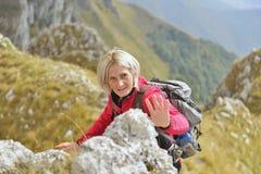 享受室外活动的愉快的资深女性远足者 免版税库存图片