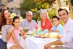 享受室外膳食的多代的家庭在庭院里 免版税库存图片