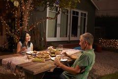 享受室外膳食的成熟夫妇在后院 库存照片