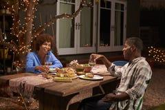 享受室外膳食的成熟夫妇在后院 图库摄影