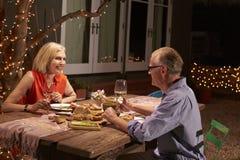 享受室外膳食的成熟夫妇在后院 库存图片