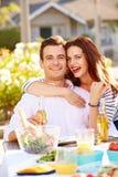 享受室外膳食的浪漫夫妇在庭院里 库存图片
