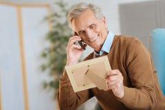 享受家庭交谈的放光的退休的绅士 免版税库存图片