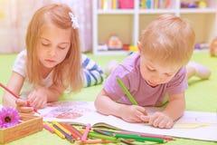 享受家庭作业的愉快的男婴&女孩 免版税库存图片