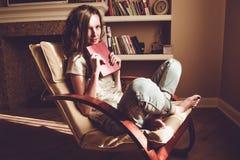 享受家庭时间 拿着与预期的俏丽的妇女纸旧书在舒适的现代椅子 自然光 舒适家 库存图片