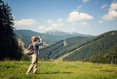 享受山景的年轻旅客 免版税库存图片